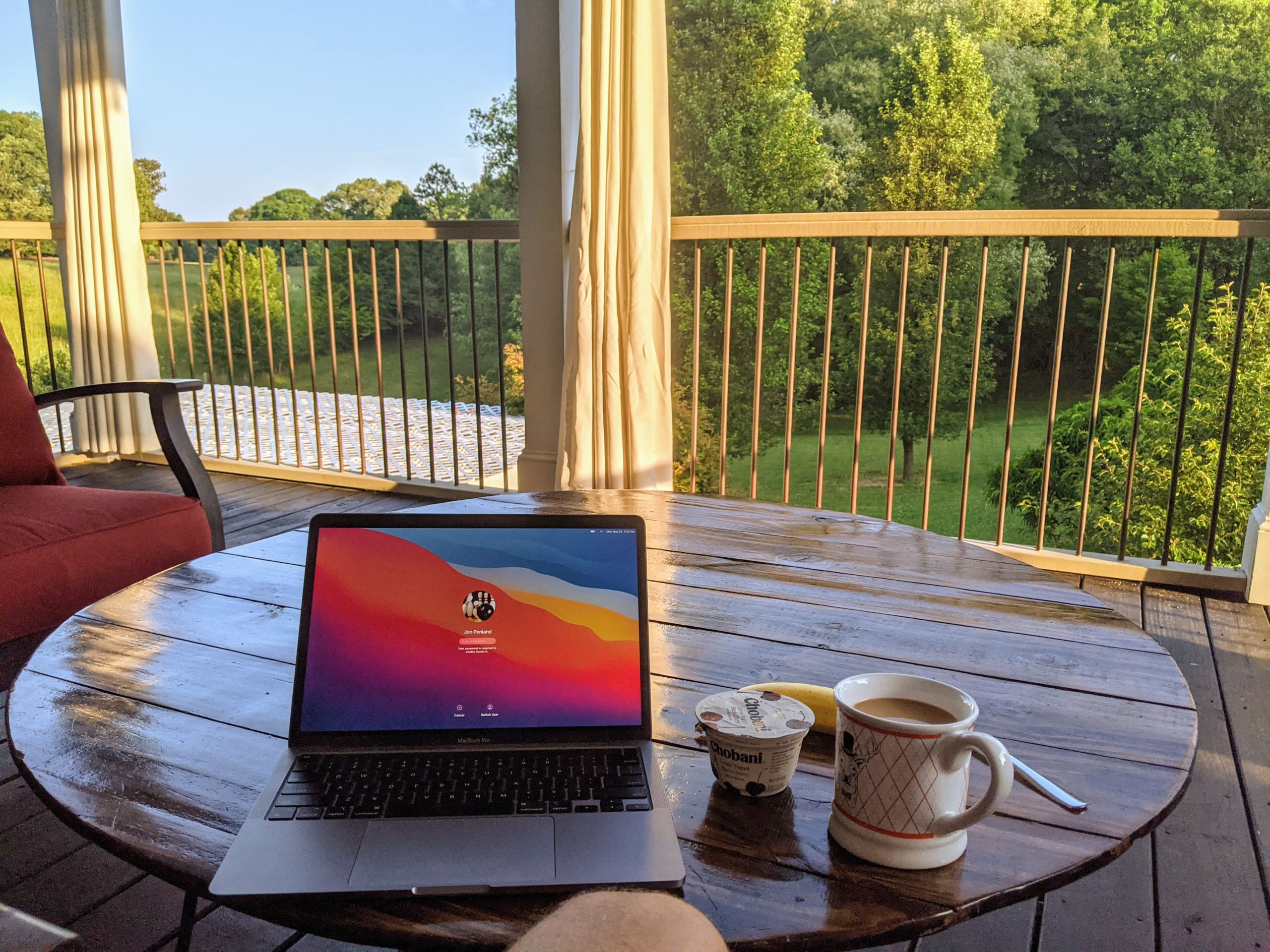Laptop and light breakfast sitting on a table overlooking a park-like backyard