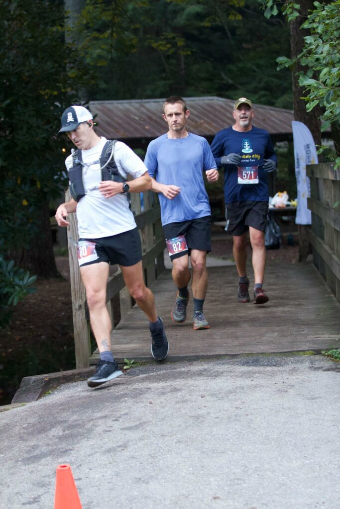 Crossing a wooden bridge surrounded by other runners.